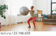 Купить «woman doing squats with fitness ball at home», видеоролик № 33748659, снято 28 марта 2020 г. (c) Syda Productions / Фотобанк Лори