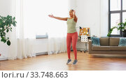 woman doing jumping jack exercise at home. Стоковое видео, видеограф Syda Productions / Фотобанк Лори