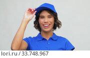 Купить «portrait of happy delivery woman in blue uniform», видеоролик № 33748967, снято 9 апреля 2020 г. (c) Syda Productions / Фотобанк Лори