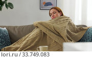 sick woman in scarf wrapping into blanket at home. Стоковое видео, видеограф Syda Productions / Фотобанк Лори