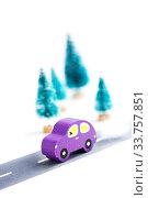Купить «Wooden car on paper road against fir-trees on white background. Traffic on country road», фото № 33757851, снято 13 мая 2020 г. (c) Papoyan Irina / Фотобанк Лори