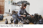 Купить «Positive young female potter working in pottery, checking quality of ceramic objects», видеоролик № 33758479, снято 31 мая 2020 г. (c) Яков Филимонов / Фотобанк Лори
