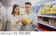 Young positive couple of customers choosing pasta in food department of supermarket. Стоковое видео, видеограф Яков Филимонов / Фотобанк Лори