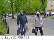 Пожилая семейная пара в защитных масках идет по улице из магазина. Эпидемия коронавируса COVID-19 в России. Калининград. Редакционное фото, фотограф Ирина Борсученко / Фотобанк Лори
