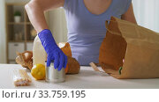 Купить «woman in gloves taking food from paper bag at home», видеоролик № 33759195, снято 3 мая 2020 г. (c) Syda Productions / Фотобанк Лори