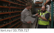 Two Caucasian male factory workers at a factory wearing vis vest and holding a pipe, standing . Стоковое видео, агентство Wavebreak Media / Фотобанк Лори