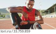 Купить «Disabled mixed race man with prosthetic legs sitting on racing track», видеоролик № 33759859, снято 17 марта 2020 г. (c) Wavebreak Media / Фотобанк Лори