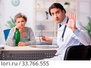 The female alcoholic visiting young male doctor. Стоковое фото, фотограф Zoonar.com/Elnur Amikishiyev / easy Fotostock / Фотобанк Лори