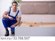 Купить «Young male contractor installing furniture at home», фото № 33768507, снято 11 ноября 2019 г. (c) Elnur / Фотобанк Лори