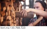 Купить «Young man woodcutter with ax puts in the log in the stand», видеоролик № 33768723, снято 2 июня 2020 г. (c) Константин Шишкин / Фотобанк Лори