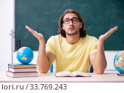 Young male geography teacher in front of blackboard. Стоковое фото, фотограф Elnur / Фотобанк Лори