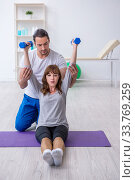 Young woman doing sport exercises with personal coach. Стоковое фото, фотограф Elnur / Фотобанк Лори