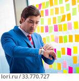 Купить «Young handsome employee with many conflicting priorities», фото № 33770727, снято 15 августа 2018 г. (c) Elnur / Фотобанк Лори