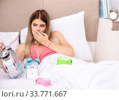 Купить «Young woman waking up in the morning in bed», фото № 33771667, снято 29 июня 2018 г. (c) Elnur / Фотобанк Лори