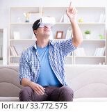 Купить «Man with virtual reality glasses playing at home», фото № 33772575, снято 16 мая 2017 г. (c) Elnur / Фотобанк Лори