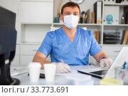 Купить «Man doctor in face mask working at laptop», фото № 33773691, снято 13 июля 2020 г. (c) Яков Филимонов / Фотобанк Лори