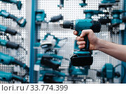 Male worker hand holds electric drill, tool store. Стоковое фото, фотограф Tryapitsyn Sergiy / Фотобанк Лори