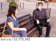 Купить «Emotional couple in protective medical masks against coronavirus communicate sittig on bench», фото № 33775343, снято 5 июля 2020 г. (c) Яков Филимонов / Фотобанк Лори