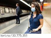 Купить «Woman in mask with earphones on subway station», фото № 33775351, снято 25 мая 2020 г. (c) Яков Филимонов / Фотобанк Лори