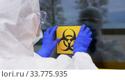 healthcare worker sticking biohazard sign to door. Стоковое видео, видеограф Syda Productions / Фотобанк Лори