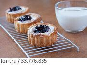 Купить «Three jam cakes and a clear mug of milk on the table, still life», фото № 33776835, снято 15 апреля 2020 г. (c) Катерина Белякина / Фотобанк Лори