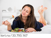 Woman in blue silk robe eats salad in bed. Стоковое фото, фотограф Яков Филимонов / Фотобанк Лори