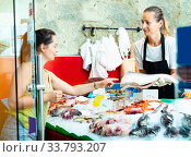 Polite female worker of fish shop in apron offering fresh raw salmon to woman customer. Стоковое фото, фотограф Яков Филимонов / Фотобанк Лори