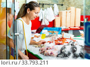 Focused woman searching for fresh seafood on icy showcase while shopping in fish store. Стоковое фото, фотограф Яков Филимонов / Фотобанк Лори
