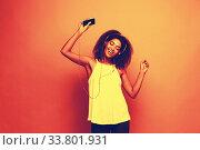 Купить «Lifestyle Concept - Portrait of beautiful African American woman joyful listening to music on mobile phone. Copy Space.», фото № 33801931, снято 6 августа 2020 г. (c) easy Fotostock / Фотобанк Лори
