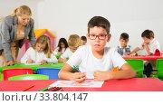 Little schoolboy drawing with color pencils. Стоковое фото, фотограф Яков Филимонов / Фотобанк Лори