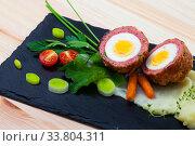 Купить «Dishes of traditional Scottish cuisine of scotch egg served with greens and potatoes», фото № 33804311, снято 5 июня 2020 г. (c) Яков Филимонов / Фотобанк Лори