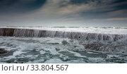 Белая пена от волн ударяющихся о волнорез. Стоковое фото, фотограф Сергей Тиняков / Фотобанк Лори