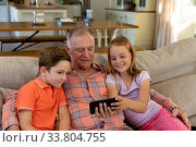 Grandfather and grandchildren at home in the living room. Стоковое фото, агентство Wavebreak Media / Фотобанк Лори