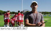 Купить «Coach taking note of rugby players performance», видеоролик № 33805867, снято 13 ноября 2019 г. (c) Wavebreak Media / Фотобанк Лори