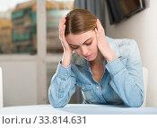 Купить «Upset woman sitting at table», фото № 33814631, снято 5 июня 2020 г. (c) Яков Филимонов / Фотобанк Лори