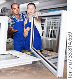 Positive workers in blue overalls assembling pvc windows. Стоковое фото, фотограф Яков Филимонов / Фотобанк Лори