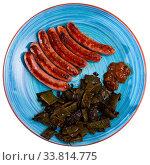 Купить «Appetizing fried sausages with green beans», фото № 33814775, снято 31 мая 2020 г. (c) Яков Филимонов / Фотобанк Лори