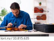 Купить «Young male repairman repairing violin», фото № 33815635, снято 25 октября 2019 г. (c) Elnur / Фотобанк Лори