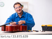 Купить «Young male repairman repairing cello», фото № 33815639, снято 25 октября 2019 г. (c) Elnur / Фотобанк Лори