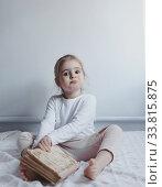 Купить «Маленькая девочка мечтает с книгой в руках», фото № 33815875, снято 10 февраля 2020 г. (c) Сергей Тиняков / Фотобанк Лори