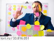 Купить «Young male employee in conflicting priorities concept», фото № 33816051, снято 4 октября 2019 г. (c) Elnur / Фотобанк Лори