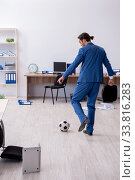 Купить «Young male employee playing football in the office», фото № 33816283, снято 13 сентября 2019 г. (c) Elnur / Фотобанк Лори