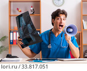 Купить «Young handsome doctor radiologyst working in clinic», фото № 33817051, снято 10 августа 2018 г. (c) Elnur / Фотобанк Лори