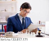 Купить «Young lawyer playing chess to train his court strategy and tacti», фото № 33817171, снято 31 июля 2018 г. (c) Elnur / Фотобанк Лори