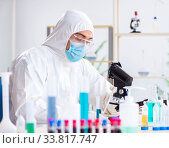 Купить «Young chemist student working in lab on chemicals», фото № 33817747, снято 27 апреля 2018 г. (c) Elnur / Фотобанк Лори