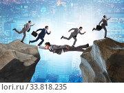 Купить «Businessman acting as a bridge in support concept», фото № 33818235, снято 3 июня 2020 г. (c) Elnur / Фотобанк Лори