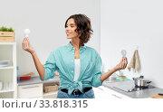 Купить «smiling woman comparing different light bulbs», фото № 33818315, снято 18 апреля 2020 г. (c) Syda Productions / Фотобанк Лори