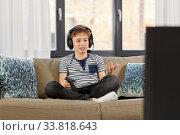 Купить «upset boy with gamepad playing video game at home», фото № 33818643, снято 10 апреля 2020 г. (c) Syda Productions / Фотобанк Лори