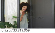 Mixed race woman opening a entrance door and looking at camera. Стоковое видео, агентство Wavebreak Media / Фотобанк Лори
