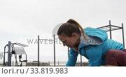 Купить «Sporty Caucasian woman exercising in an outdoor gym during daytime», видеоролик № 33819983, снято 8 августа 2019 г. (c) Wavebreak Media / Фотобанк Лори